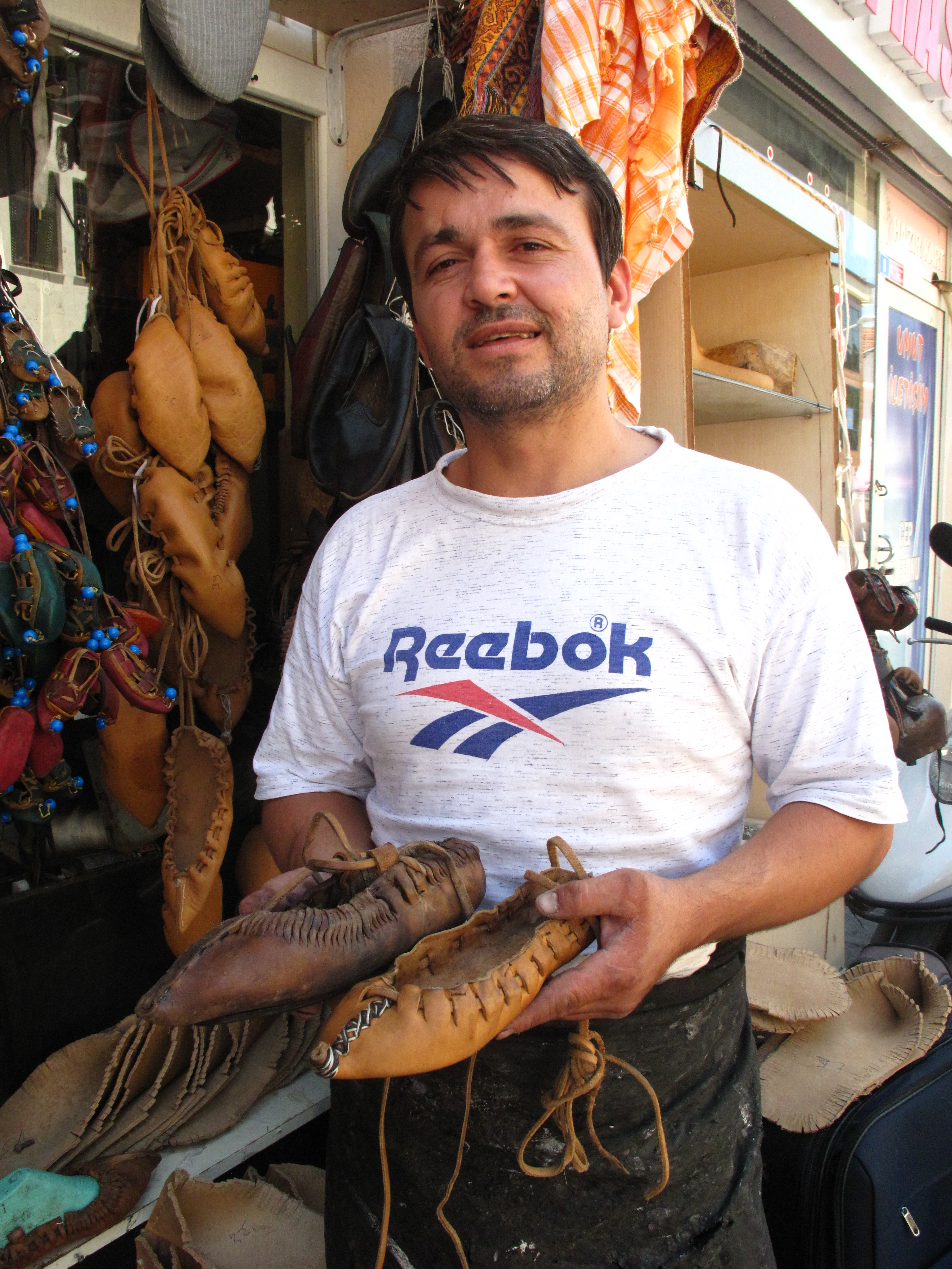 sandal maker Tunahan with some of his traditional sandals