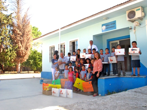 The children, headmaster and teacher pose for a photo outside the school entrance with Dean and Jane